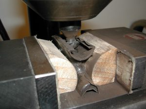 The cutter touching the back of the mortise; ntoe the loosened tape.