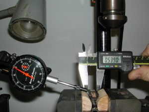 Positioning the frog in the milling vise using the dial indicator and the vernier calipers.